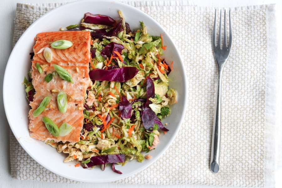 salmon in a bowl with asian Brussel sprout salad under it.