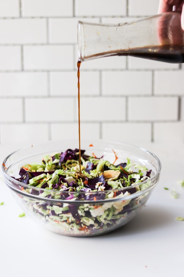 Dressing being poured over a salad.