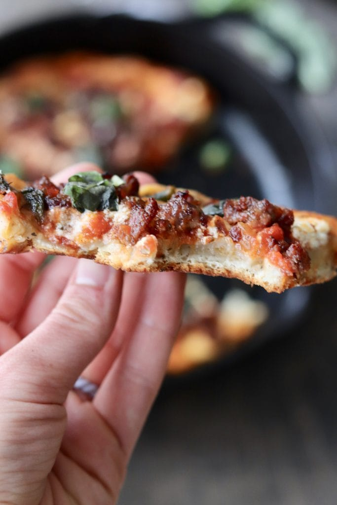 A hand holding a piece of pizza.
