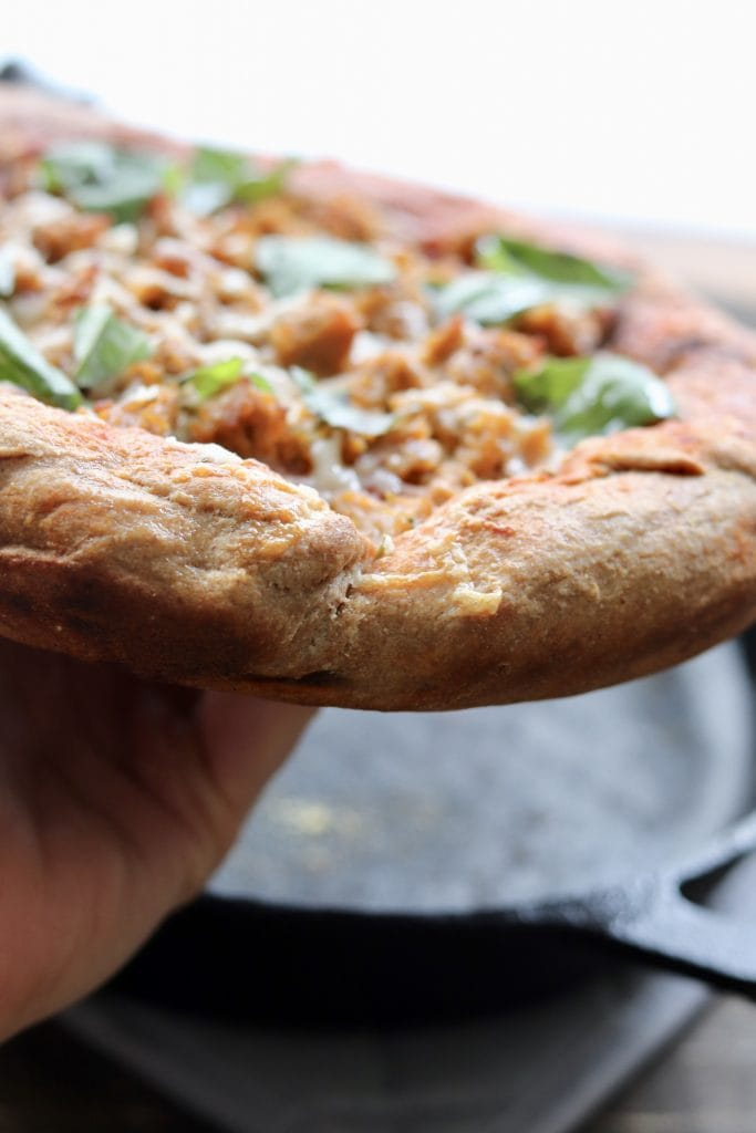 A side view of chicken sausage pizza.