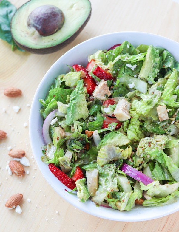 Strawberry avocado summer salad with chicken- featuring a crunchy romaine, cucumber, red onion, chopped nuts and pungent cheese then tossed in honey basil vinaigrette makes for the ultimate summer salad combo that will leave you feeling satisfied #avocado #strawberries #salad #summersalad #mealprep #masonjarsalad | Mealswithmaggie.com