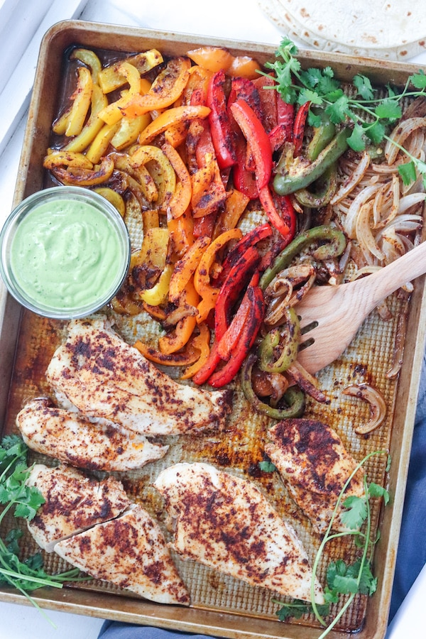 These one sheet pan chicken fajitas with avocado sauce can be made in under 30 minutes and is an easy clean up! Peppers, avocado and low sodium fajita seasoning makes for a heart healthy meal. | mealswithmaggie.com #hearthealthy #onesheetpandinner #onesheetpanchickenfajitas #avocadosauce #lowsodiumfajitas #quickandeasydinner #mealprep